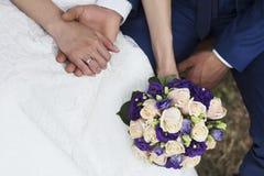 Manos de la novia y del novio con las flores Fotos de archivo libres de regalías