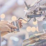 Manos de la opinión del primer del barista profesional que trabajan en un café que prepara el café del café express, en la máquin Fotos de archivo