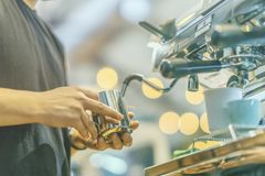 Manos de la opinión del primer del barista profesional que trabajan en un café que prepara el café del café express, en la máquin Foto de archivo libre de regalías
