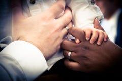 Manos de la pareja interracial con el niño Imagen de archivo
