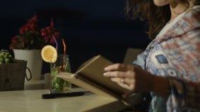 Manos de la poesía inspirada de la escritura de la mujer en libreta en el restaurante al aire libre en la noche almacen de metraje de vídeo