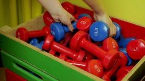 Manos de la señora juguetona que ponen pesas de gimnasia en la caja después de entrenamiento activo en gimnasio almacen de video