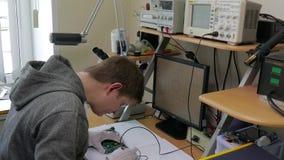 Manos de la tecnología profesional que reparan componentes de pequeño ordenador en la tabla del microscopio usando el soldador pr metrajes