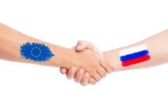 Manos de la unión europea y de Rusia que sacuden con las banderas Fotografía de archivo libre de regalías