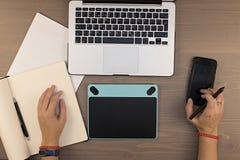 manos de la visión superior en la tabla, la tableta del dibujo, el ordenador portátil y el teléfono como fotografía de archivo