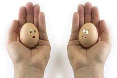 Manos de las caras de los huevos Imágenes de archivo libres de regalías