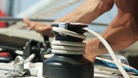 Manos de las cuerdas de tracción masculinas del dueño de un yate en los yahts almacen de metraje de vídeo