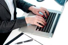 Manos de las hembras que pulsan en la computadora portátil fotografía de archivo libre de regalías