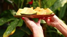Manos de las mujeres con el melón en un cuenco de madera Fondo tropical almacen de metraje de vídeo