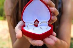 Manos de las mujeres con una caja roja del terciopelo con un par de anillos de bodas del oro Fotos de archivo