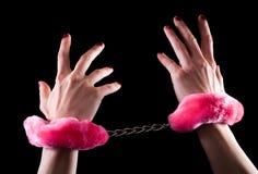 Manos de las mujeres jovenes en esposas con la piel rosada Imágenes de archivo libres de regalías