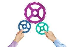 Manos de las ruedas dentadas del concepto del trabajo en equipo Fotografía de archivo