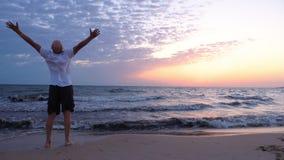 Manos de levantamiento del hombre libre en la playa en la salida del sol sobre el mar almacen de video