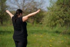 Manos de levantamiento de la mujer gorda, visi?n desde la parte posterior foto de archivo