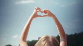 Manos de levantamiento de la mujer joven a un cielo en la forma del corazón almacen de video