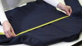 Manos de limpiar en seco la chaqueta de medición del empleado metrajes