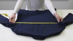 Manos de limpiar en seco la ropa de medición del trabajador almacen de video