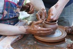 Manos de los alfareros que crean un crisol de arcilla Imagen de archivo libre de regalías