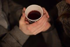 Manos de los amantes jovenes que sostienen una taza caliente de té Fotos de archivo