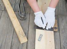 Manos de los carpinteros usando el lápiz y la regla Fotos de archivo libres de regalías