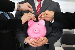 Manos de los empresarios con las monedas y el piggybank Foto de archivo