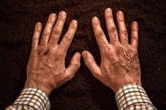 Manos de los granjeros en la tierra del suelo fértil imágenes de archivo libres de regalías