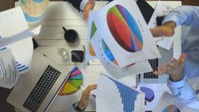 Manos de los hombres de negocios que celebran el logro que lanza para arriba documentos con los gráficos Trabajadores que disfrut metrajes