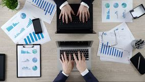 Manos de los hombres de negocios que mecanografían en los ordenadores portátiles enfrente de uno a, visión superior divertida foto de archivo