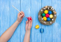 Manos de los huevos de Pascua de la pintura de la muchacha con un cepillo y una pintura en una tabla azul de madera en la cual ha fotografía de archivo libre de regalías