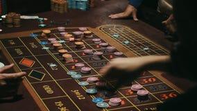 Manos de los jugadores que apuestan a la tabla de la ruleta Superficie de juego del marrón de la tabla del casino metrajes