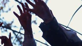 Manos de los monstruos locos que sacuden en aire, pesadilla asustadiza, ataque total del zombi almacen de video