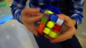 Manos de los muchachos que solucionan el cubo del rubik almacen de video