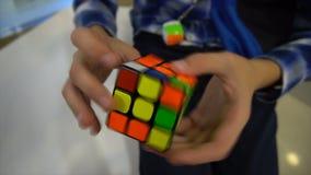 Manos de los muchachos que solucionan el cubo del rubik almacen de metraje de vídeo