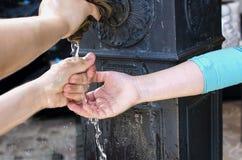 Manos de los niños con el chapoteo del agua imagen de archivo
