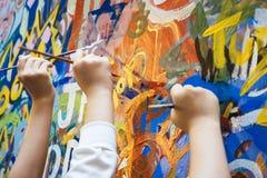 Manos de los niños con el fondo colorido de la pintura Foto de archivo libre de regalías