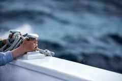 Manos de los niños mientras que sostiene el bolardo del barco Foto de archivo