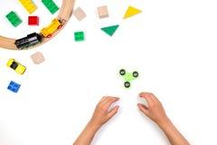 Manos de los niños que juegan con el juguete del hilandero de la persona agitada Muchos juguetes coloridos en el fondo blanco Foto de archivo