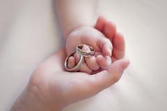 Manos de los niños que llevan a cabo los anillos de plata del oro imagen de archivo libre de regalías