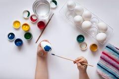 Manos de los niños que pintan los huevos en el fondo blanco Fotos de archivo libres de regalías