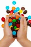 Manos de los niños que sostienen el caramelo del color Imagen de archivo libre de regalías