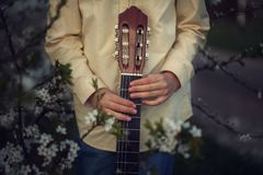 Manos de los niños que sostienen la guitarra en fondo de la naturaleza Imagen de archivo libre de regalías
