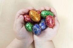 Manos de los niños que sostienen los huevos de Pascua Fotos de archivo