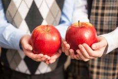 Manos de los niños que sostienen una manzana Fotos de archivo libres de regalías