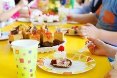 Manos de los niños que comen las pequeñas tortas deliciosas en la tabla amarilla Foto de archivo libre de regalías