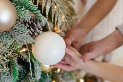 Manos de los padres que llevan a cabo las manos de los niños que sostienen una bola grande de la Navidad blanca Adorne el árbol d imagenes de archivo