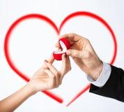 Manos de los pares con el anillo de compromiso Imagen de archivo libre de regalías