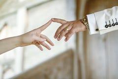 Manos de los pares de la boda que tocan los dedos índices Imágenes de archivo libres de regalías