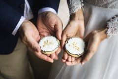 Manos de los pares del recién casado que celebran mostrar las galletas que se casan Celebratio fotografía de archivo libre de regalías
