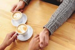 Manos de los pares en una tabla de madera con café Foto de archivo libre de regalías