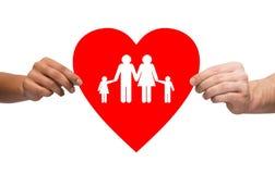 Manos de los pares que llevan a cabo el corazón rojo con la familia Imágenes de archivo libres de regalías